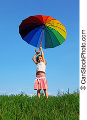 smiling girl stands on green grass on blue sky background with colored umbrella aloft over his head in his hands
