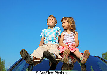 little boy and girl sitting on car roof on blue sky