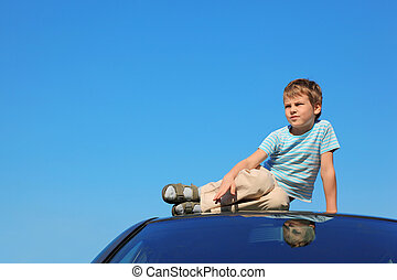 serious boy sitting on roof of car, blue sky