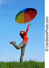 girl standing on one leg on green grass with colorful umbrellas aloft in hand against blue sky