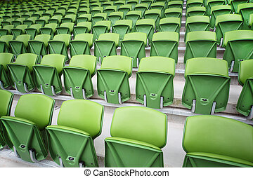 Rows of folded, green, plastic seats in very big, empty stadium. Focus on the front seats