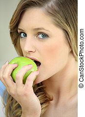 Girl eating a crisp green apple
