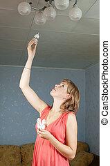 Girl changes light bulb
