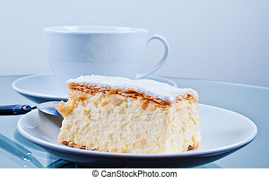 Cake Napoleon on table with cup
