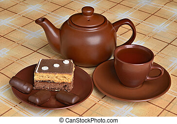 Teapot, a cup of tea, cakes and sweets on the table
