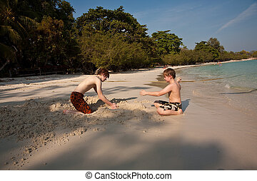 young boys are enjoying playing at the beach and building figures out of sand at the beautiful white beach