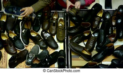 People choose shoes at stall,Various varieties of styles.