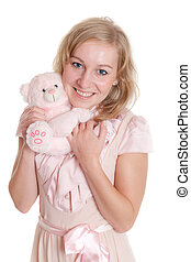 Childhood toy - The girl in a pink dress with a soft toy