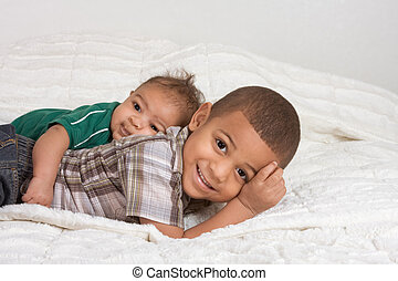 Two multiethnic boys brothers of mixed race one 3 months old...