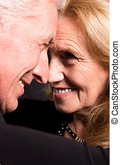 happy old couple - cute od couple posing on a black