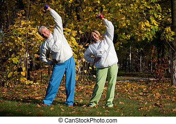 old people with dumb bells at nature