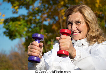 elderly woman with dumb bells - old woman with dumb bells at...
