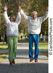 active old people jumping - cute active old people in a park