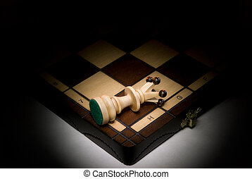 Victory or defeat - White a queen on a chess board. A dark...