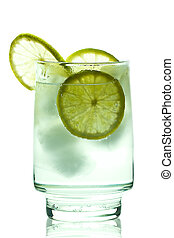 Glass of gin and tonic with ice cubes and lime slices....