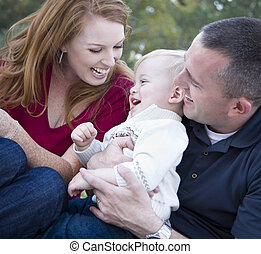 Attractive Young Parents Laughing with Child Boy in Park -...