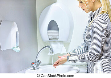 woman washing hands in restroom - blue hair woman washing...