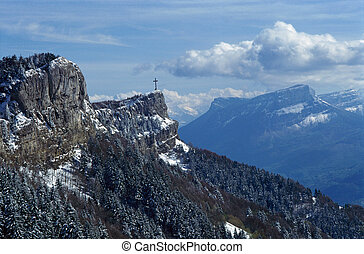 Cross and mountains near Chambery, France - Snowed cross of...