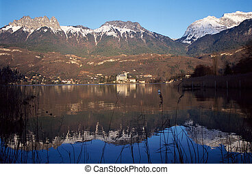 Snowed mountains and castle reflecting in lake Annecy -...