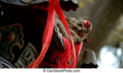 Dragon and metal bell on censer,Red ribbon blowing in wind.