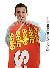 Retail shopkeeper with sale sign, - A shopkeeper holding a...