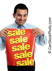 Retailer with sale sign - A male salesman holding a sale...