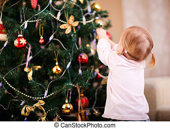 Little girl decorating Christmas tree - Back view of toddler...