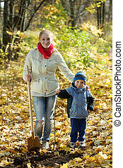 woman with her son making orchard in autumn - young woman...