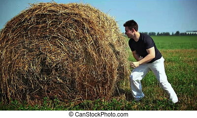 Fighting with haystack - Young man fighting with haystack.
