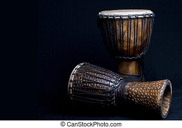 djembe - Two carved African djembe drums on dark background....
