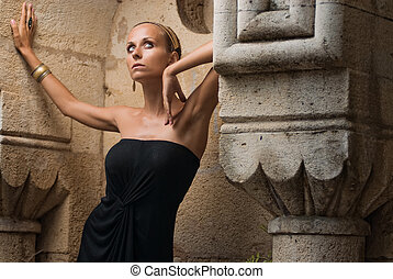 godess - girl posing in old ruins in a black dress