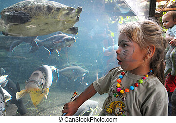 Little girl staying next to an aquarium