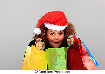 Beautiful young woman wearing a Santa hat and holding...