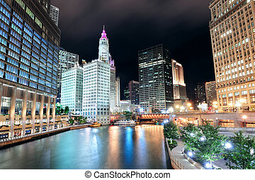 Chicago River Walk with urban skyscrapers illuminated with...