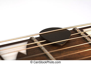 Guitar pick - Close-up of a guitar pick within the strings