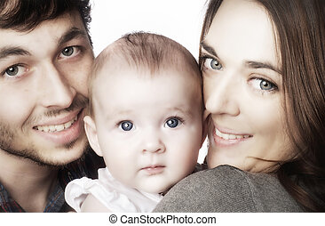 Young couple hugging their baby girl. Image isolated against...
