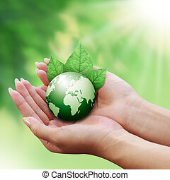 human hands holding green earth with a leaf on natrue