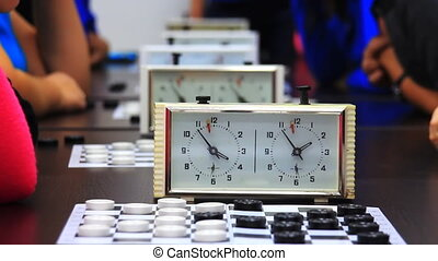 Close-up of checkers game tournament with clock. Time lapse