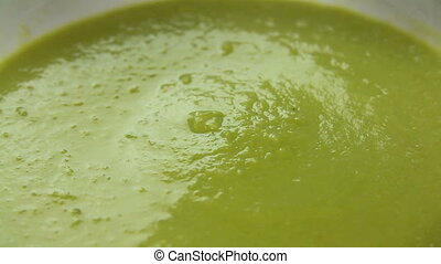 Pouring Pea Soup - Close up of pea soup being poured into a...