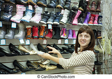 woman chooses shoes - woman shopping at fashion shoe store