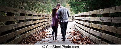 Engaged Couple - Young engaged couple walking along a wooden...