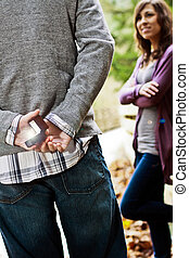 Engaged Couple - Young woman looking at a young man holding...