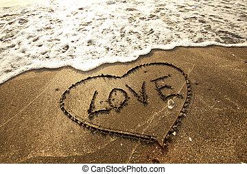 Love concept handwritten on sand
