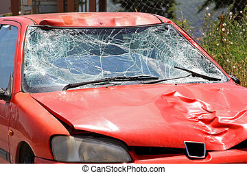 Broken windscreen at red car in traffic accident