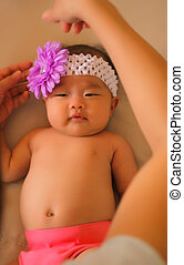 Asian Baby Girl - An infant asian girl with a purple flower...