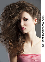beauty fashion portrait of beautiful young brunette with curly hair flying and creative hairstyle, she looks in to the lens and her face is turned of three-quarters.
