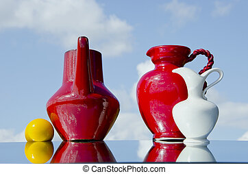 jugs and yellow ball on mirror