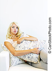 Serious woman with cushion on couch - Thoughtful beautiful...