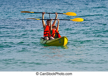 father and son are paddling with a canoe on open sea