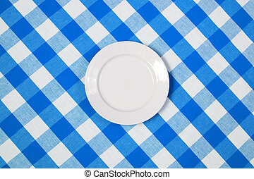 white round plate on blue checked tablecloth